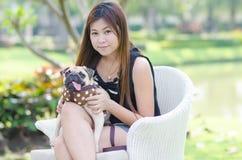Χαριτωμένη ασιατική χαλάρωση αγκαλιάσματος κοριτσιών στο πάρκο με το σκυλί μαλαγμένου πηλού κουταβιών Στοκ εικόνες με δικαίωμα ελεύθερης χρήσης