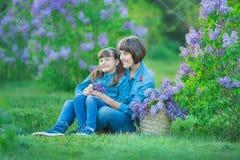 Χαριτωμένη λατρευτή όμορφη γυναικεία mom γυναίκα μητέρων με την κόρη κοριτσιών brunette στο λιβάδι του ιώδους πορφυρού θάμνου Άνθ Στοκ φωτογραφία με δικαίωμα ελεύθερης χρήσης