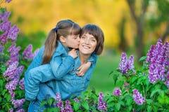 Χαριτωμένη λατρευτή όμορφη γυναικεία mom γυναίκα μητέρων με την κόρη κοριτσιών brunette στο λιβάδι του ιώδους πορφυρού θάμνου Άνθ Στοκ εικόνες με δικαίωμα ελεύθερης χρήσης