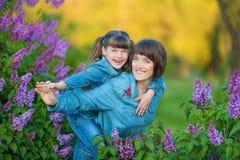 Χαριτωμένη λατρευτή όμορφη γυναικεία mom γυναίκα μητέρων με την κόρη κοριτσιών brunette στο λιβάδι του ιώδους πορφυρού θάμνου Άνθ Στοκ φωτογραφίες με δικαίωμα ελεύθερης χρήσης