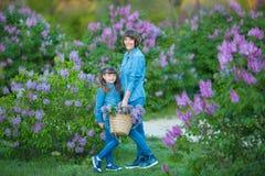 Χαριτωμένη λατρευτή όμορφη γυναικεία mom γυναίκα μητέρων με την κόρη κοριτσιών brunette στο λιβάδι του ιώδους πορφυρού θάμνου Άνθ Στοκ Εικόνες