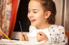 Χαριτωμένη βούρτσα ζωγραφικής εκμετάλλευσης κοριτσιών χαμόγελου Στοκ Εικόνες