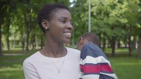 Χαριτωμένη γυναίκα αφροαμερικάνων πορτρέτου που κρατά τον αστείο γιο της στα όπλα της στο πράσινο πάρκο κοντά επάνω Αγαπώντας οικ απόθεμα βίντεο