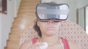 Χαριτωμένη γυναίκα αφροαμερικάνων πορτρέτου που φορά στην κάσκα εικονικής πραγματικότητας που χρησιμοποιεί τη συνεδρίαση πηδαλίων φιλμ μικρού μήκους