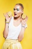 Χαριτωμένη γυναίκα με τη φέτα των λεμονιών υπό εξέταση Στοκ φωτογραφία με δικαίωμα ελεύθερης χρήσης