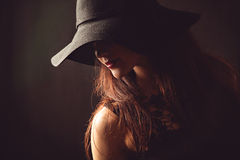 Χαριτωμένη γυναίκα με τις μακριές τρίχες στο μαύρο καπέλο Στοκ Εικόνες