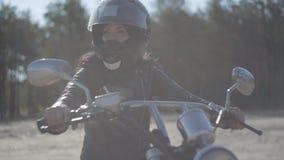 Χαριτωμένη γυναίκα πορτρέτου που φορά τη μαύρη συνεδρίαση κρανών στη μοτοσικλέτα που κοιτάζει μακριά Χόμπι, ταξίδι και ενεργός τρ απόθεμα βίντεο