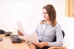 Χαριτωμένη γυναίκα που διαβάζει ένα έγγραφο στο γραφείο Στοκ Εικόνα