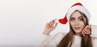Χαριτωμένη γυναίκα που εξετάζει τη κάμερα και που το καπέλο Χριστουγέννων της Στοκ εικόνα με δικαίωμα ελεύθερης χρήσης