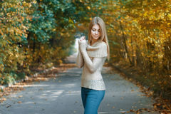 Χαριτωμένη γυναίκα σε ένα Τζέρσεϋ που στέκεται στο πάρκο φθινοπώρου Στοκ εικόνα με δικαίωμα ελεύθερης χρήσης