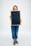 Χαριτωμένη γυναίκα σπουδαστής που κρατά τον κενό πίνακα Στοκ φωτογραφίες με δικαίωμα ελεύθερης χρήσης