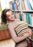 Χαριτωμένη γυναίκα σπουδαστής σε μια βιβλιοθήκη Στοκ φωτογραφίες με δικαίωμα ελεύθερης χρήσης