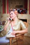 Χαριτωμένη γυναίκα στα ρόλερ μπουρνουζιών και τρίχας που μιλούν στο τηλέφωνο καθμένος στην κουζίνα στοκ φωτογραφία με δικαίωμα ελεύθερης χρήσης