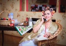 Χαριτωμένη γυναίκα στα ρόλερ μπουρνουζιών και τρίχας που μιλούν στο τηλέφωνο καθμένος στην κουζίνα στοκ φωτογραφίες