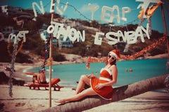 Χαριτωμένη γυναίκα στο κόκκινα φόρεμα, τα γυαλιά ηλίου και τη συνεδρίαση καπέλων santa στο φοίνικα στην εξωτική τροπική παραλία Έ Στοκ Φωτογραφίες
