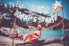 Χαριτωμένη γυναίκα στο κόκκινα φόρεμα, τα γυαλιά ηλίου και τη συνεδρίαση καπέλων santa στο φοίνικα στην εξωτική τροπική παραλία Έ Στοκ Φωτογραφία