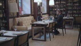 Χαριτωμένη γυναίκα brunette και ξανθή γενειοφόρος συνεδρίαση ανδρών στον πίνακα στην εργασία καφέδων Το lap-top, τα έγγραφα και τ απόθεμα βίντεο