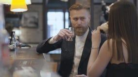 Χαριτωμένη γυναίκα brunette και ξανθή γενειοφόρος συνεδρίαση ανδρών αντίθετο στενό στον επάνω φραγμών Έννοια του τρόπου ζωής νύχτ απόθεμα βίντεο