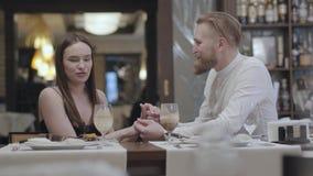 Χαριτωμένη γυναίκα brunette πορτρέτου και μια όμορφη γενειοφόρος ξανθή συνεδρίαση ανδρών στον πίνακα ο ένας μπροστά από τον άλλον απόθεμα βίντεο