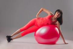 Χαριτωμένη γυναίκα brunette που κάνει τις ασκήσεις με το fitball Στοκ Εικόνες