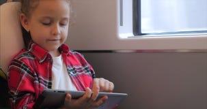 Χαριτωμένη διασκέδαση μικρών κοριτσιών με την ταμπλέτα Ο ελεύθερος χρόνος εξόδων παιδιών, οδηγά ένα ηλεκτρικό τραίνο, παίζοντας τ απόθεμα βίντεο