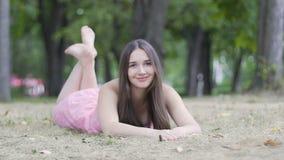 Χαριτωμένη ελκυστική γυναίκα που βρίσκεται στη χλόη που χαμογελά, χαλαρωμένο κορίτσι να ονειρευτεί πάρκων αργό φιλμ μικρού μήκους