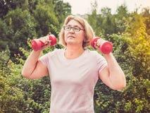 Χαριτωμένη, ενήλικη γυναίκα που κάνει τις ασκήσεις με τους ρόδινους αλτήρες στοκ φωτογραφίες