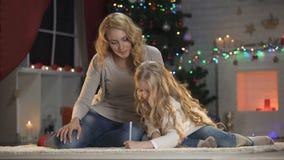 Χαριτωμένη επιστολή γραψίματος κοριτσιών για Santa με το mom, το χριστουγεννιάτικο δέντρο και το σπινθήρισμα φω'των φιλμ μικρού μήκους