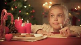 Χαριτωμένη επιστολή γραψίματος κοριτσιών για Santa στον πίνακα που διακοσμείται για τα Χριστούγεννα, λίστα επιθυμητών στόχων απόθεμα βίντεο