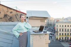 Χαριτωμένη επιχειρηματίας που μιλά στο τηλέφωνο που στέκεται στη στέγη του σπιτιού στην παλαιά πόλη Δίπλα σε το είναι ένα lap-top Στοκ εικόνες με δικαίωμα ελεύθερης χρήσης