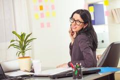 Χαριτωμένη επιχειρηματίας στο τηλέφωνο στο γραφείο της Στοκ φωτογραφία με δικαίωμα ελεύθερης χρήσης