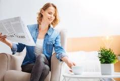 Χαριτωμένη ευχάριστη γυναίκα που απολαμβάνει την εφημερίδα πίνοντας το τσάι στοκ φωτογραφίες