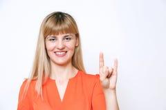 Χαριτωμένη εύθυμη γυναίκα που εμφανίζει σημάδι χεριών ειρήνης/νίκης agains Στοκ Εικόνες