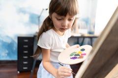 Χαριτωμένη ζωγραφική κοριτσιών liitle κινηματογραφήσεων σε πρώτο πλάνο μέσα στο σπίτι της Έννοια του αυτιού στοκ φωτογραφία με δικαίωμα ελεύθερης χρήσης