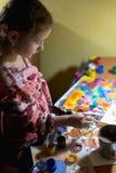 Χαριτωμένη ζωγραφική μικρών κοριτσιών με το πινέλο και τα ζωηρόχρωμα χρώματα Στοκ φωτογραφία με δικαίωμα ελεύθερης χρήσης