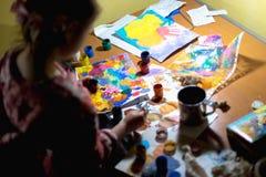 Χαριτωμένη ζωγραφική μικρών κοριτσιών με το πινέλο και τα ζωηρόχρωμα χρώματα Στοκ Φωτογραφίες