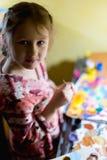 Χαριτωμένη ζωγραφική μικρών κοριτσιών με το πινέλο και τα ζωηρόχρωμα χρώματα Στοκ Εικόνες