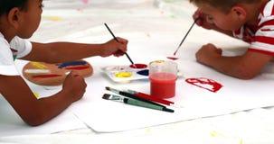 Χαριτωμένη ζωγραφική μικρών παιδιών που βρίσκεται σε χαρτί απόθεμα βίντεο