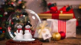 Χαριτωμένη ζωτικότητα Χριστουγέννων του ζεύγους χιονανθρώπων στη σφαίρα χιονιού απόθεμα βίντεο