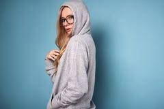 Χαριτωμένη θετική ξανθή γυναίκα στο γκρίζα hoodie και τα γυαλιά Στοκ εικόνα με δικαίωμα ελεύθερης χρήσης