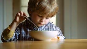 Χαριτωμένη κατανάλωση μωρών Μικρό παιδί που έχει το πρόγευμα στην κουζίνα Το ευτυχές κουτάλι αγοράκι τρώεται Μωρό που τρώει τα τρ απόθεμα βίντεο