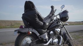 Χαριτωμένη καυκάσια γυναίκα σε ένα μαύρο σακάκι και τα εσώρουχα δέρματος που βρίσκονται σε μια κλασική μοτοσικλέτα Χόμπι, που ταξ απόθεμα βίντεο