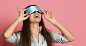 Χαριτωμένη καυκάσια γυναίκα στη μάσκα ύπνου που έχει τη διασκέδαση πέρα από το ρόδινο υπόβαθρο στοκ εικόνες