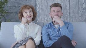 Χαριτωμένη κομψή ώριμη γυναίκα πορτρέτου που μιλά με το νεαρό άνδρα στην μπλε συνεδρίαση πουκάμισων στο σπίτι στον καναπέ κοντά ε απόθεμα βίντεο