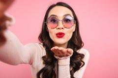 Χαριτωμένη κυρία στο περιστασιακό πουκάμισο με τα κόκκινα χείλια που φορούν γύρω από τα γυαλιά ηλίου Στοκ Φωτογραφία