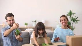 Χαριτωμένη κόρη παιδιών που βοηθά τους γονείς που ανοίγουν τα κιβώτια στο νέο σπίτι απόθεμα βίντεο