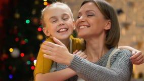 Χαριτωμένη κόρη που αγκαλιάζει τη μητέρα, που απολαμβάνει τις διακοπές Χριστουγέννων μαζί, κινηματογράφηση σε πρώτο πλάνο απόθεμα βίντεο