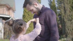 Χαριτωμένη κόρη που κουμπώνει το κουμπί του μπαμπά χαμόγελού της σε ένα πουκάμισο καρό στο υπόβαθρο του σπιτιού εξοχικών σπιτιών απόθεμα βίντεο