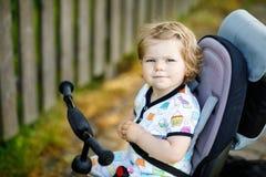 Χαριτωμένη λατρευτή συνεδρίαση κοριτσιών μικρών παιδιών στην ώθηση bicyle ή το τρίκυκλο Λίγο παιδί μωρών που συνεχίζεται για έναν στοκ εικόνες με δικαίωμα ελεύθερης χρήσης