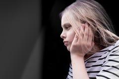 Χαριτωμένη μαθήτρια συνεδρίασης μικρών κοριτσιών που σκέφτεται στο υπόβαθρο του ανοίγματος παραθύρων Στοκ Εικόνες